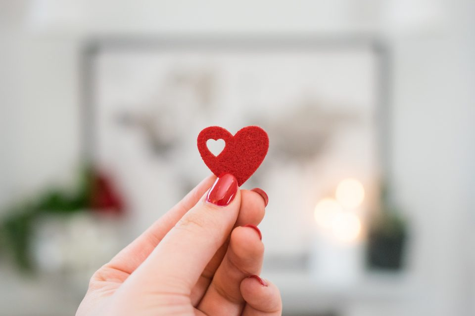 hand holding a small paper heart