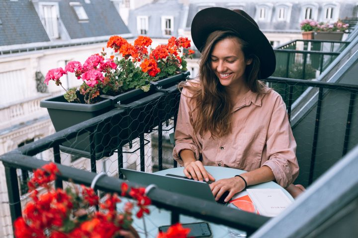 young woman smiling working on a balcony